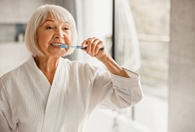 An older woman wearing a bathrobe and brushing her teeth in the mirror of her bathroom