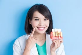 A dental professional pointing to her smile while holding a mouth mold with a dental implant in it