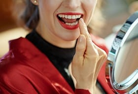 A woman wearing red lipstick and pointing to a specific tooth while looking in the mirror