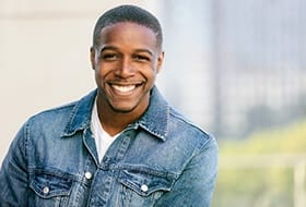 A young man wearing a denim jacket and smiling after having TMJ Therapy performed