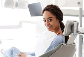 A young woman smiling while waiting to see her dentist for a regular checkup and cleaning