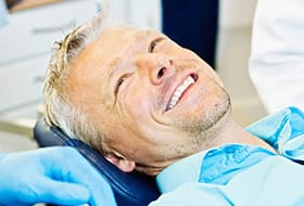 man in blue smiling at dentist
