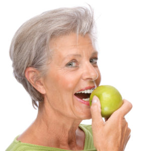 woman smiling biting into apple