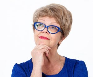 older woman thinking blue glasses