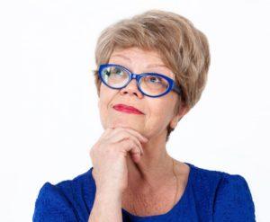 older woman thinking blue glasses