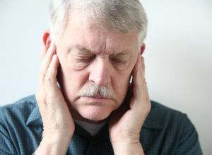 older man holding jaw in pain