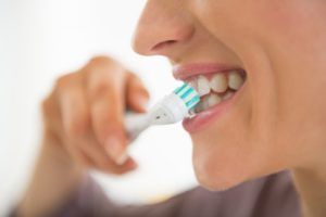 : Person with beautiful smile from a dentist in Gramercy Park brushing teeth